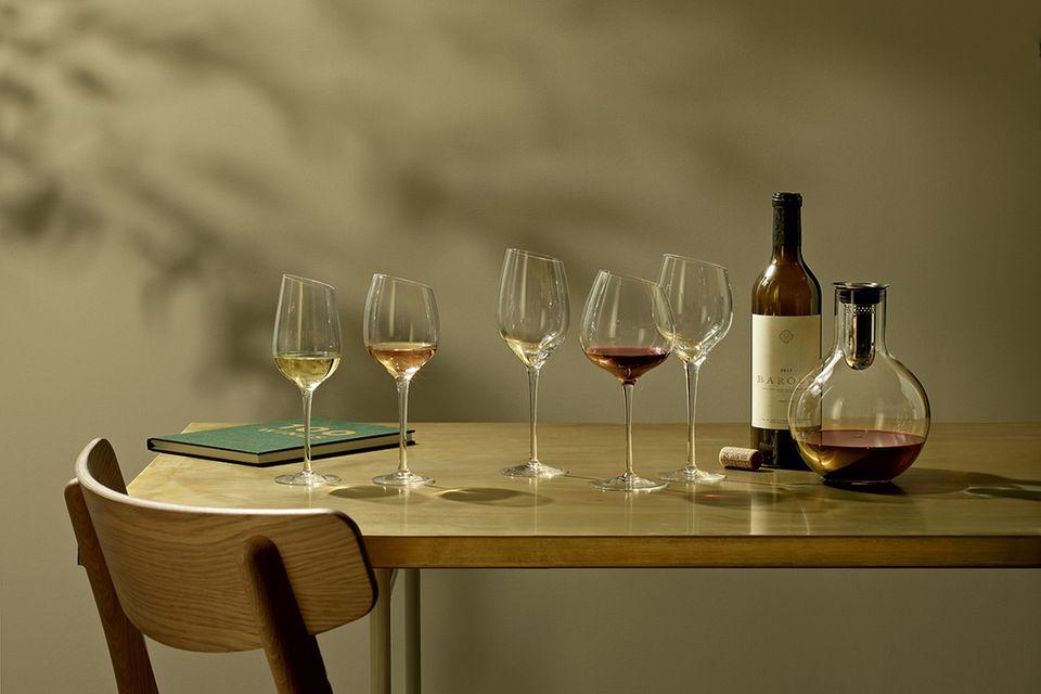Verschiedene Weingläser auf einem Tisch neben einer Flasche Wein und einer Dekantierkaraffe