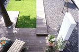 Terrasse aus Holz mit Kiesbeet und kleiner Grünfläche