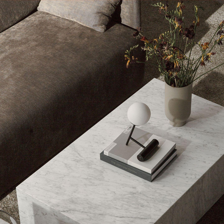 """Tischleuchte """"Phare Lamp"""" von Menu auf einem Marmor-Couchtisch mit zwei Büchern und einer Vase"""