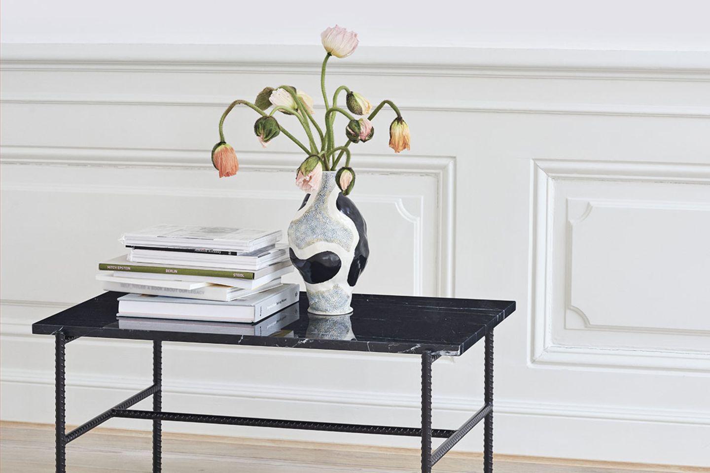 """Beistelltisch """"Rebar"""" von Hay mit mehreren Coffee Table Books und ein paar Blumen in der Vase, die die Köpfe hängen lassen"""