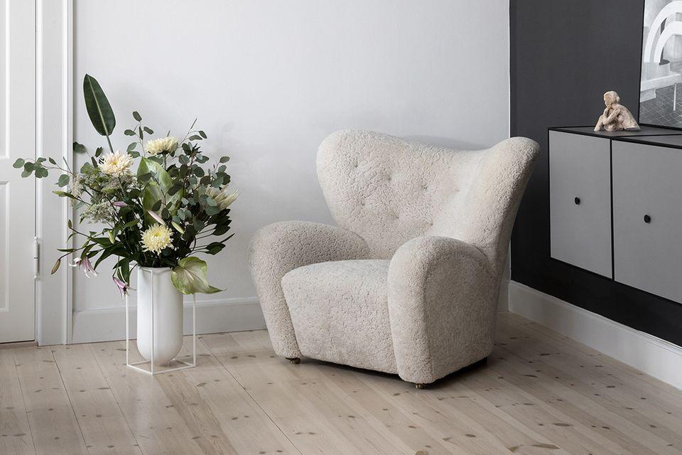 """Bodenvase """"Nolia"""" mit üppigen Blumenstrauß neben dem Sessel """"The Tired Man"""" – beides von byLassen"""