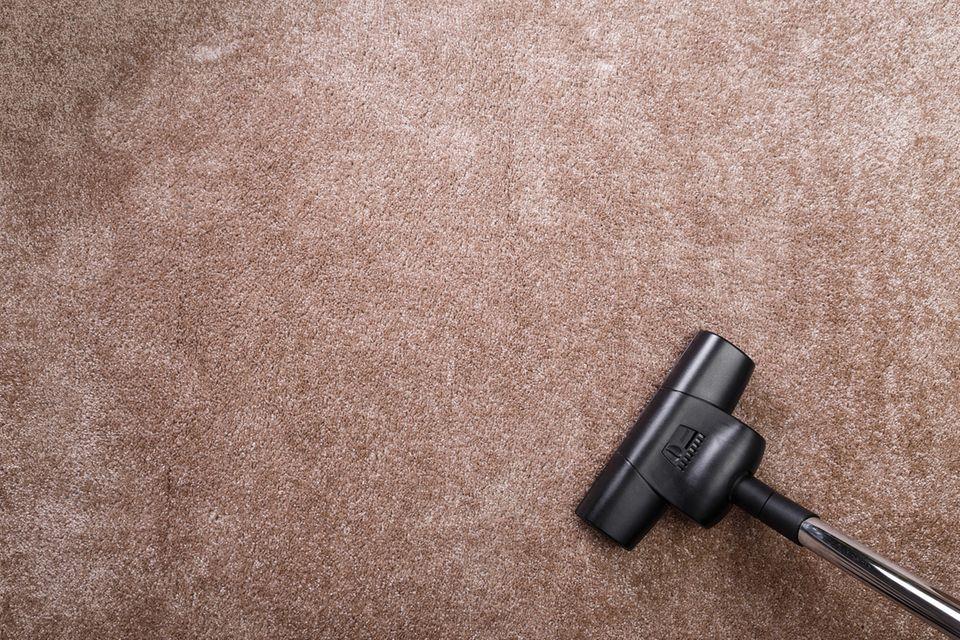 Blick von oben auf einen brauen Teppichboden mit einem Staubsauger