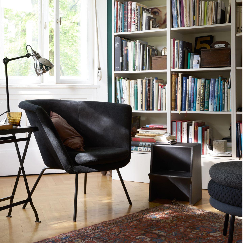 Schwarzer Tritt neben schwarzem Sessel vor Bücherregal