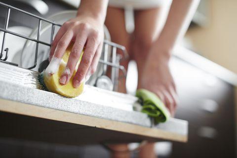 Frau reinigt den Rand der Spülmaschinentür mit einem Schwamm