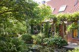 Garteteich am Haus mit Bäumen und Wasserpflanzen