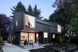 Holzhaus mit großer Fensterfront im Obergeschoss