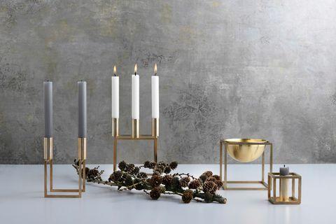 Kerzenhalter und Schalen aus Messing von By Lassen vor einer grauen Wand