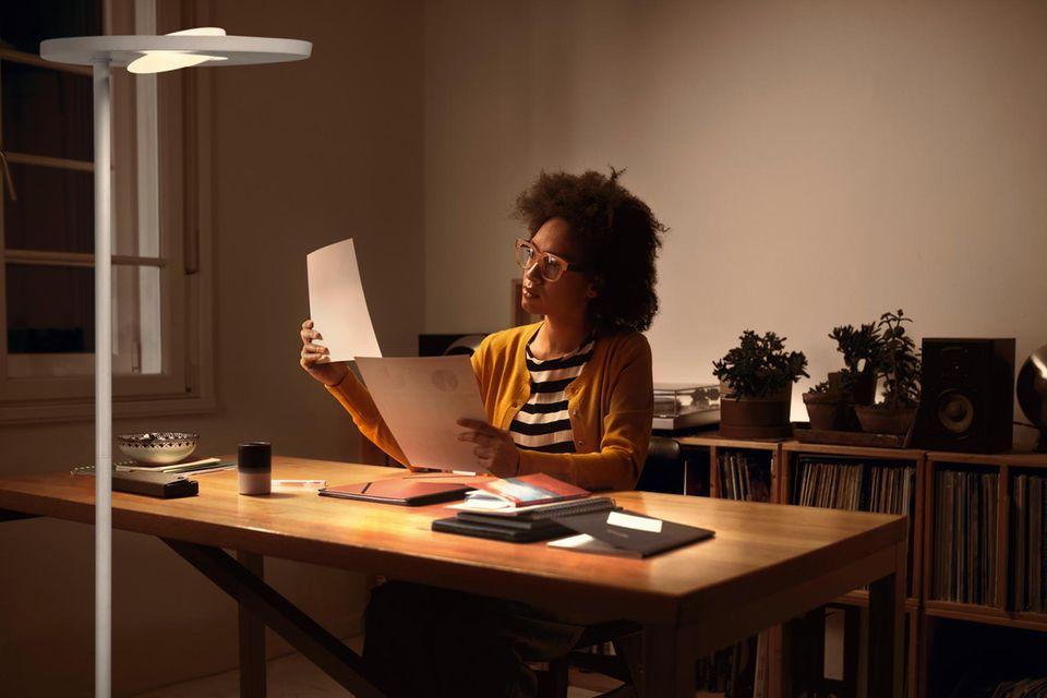 Frau im Homeoffice, am Schreibtisch sitzend bei Schreibtischlicht