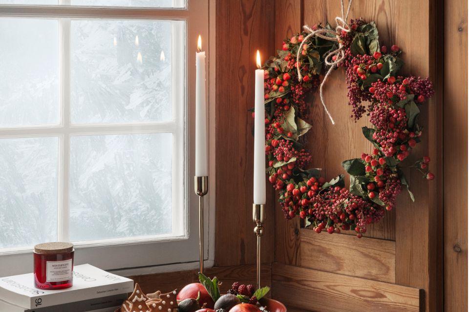 Rot-grüner Kranz hängend an einer Holzverkleidung nahe einem Fenster