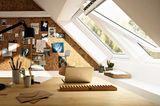 Helles Dachzimmer mit Schreibtisch, Laptop und geöffneten Dachfenstern