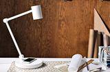 Weiße Schreibtischlampe mit Ladepad vor dunkler Holzwand auf einem Schreibtisch