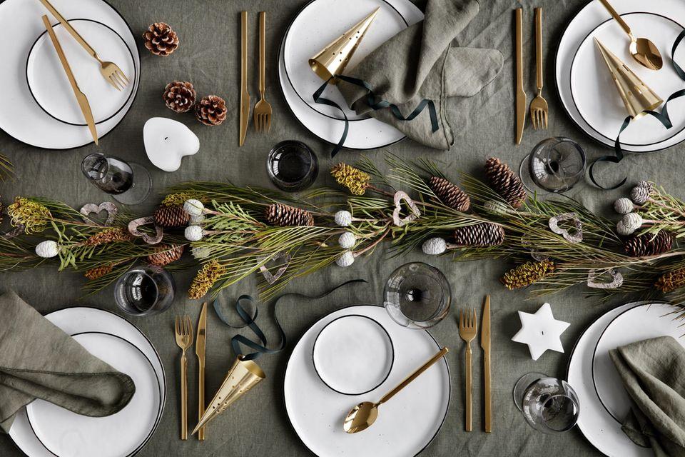 Weihnachtlich dekorierter Tisch mit hellem Geschirr, goldenem Besteck und Tannengesteck